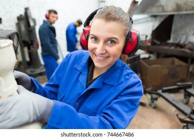 female worker wearing earmuffs in noisy workshop