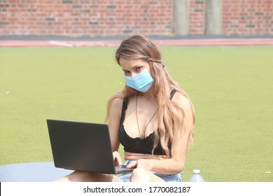 female working a computer outdoors practicing social distancing