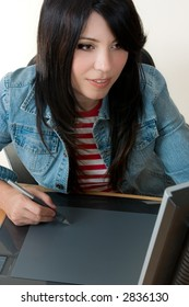 A female working with a graphic tablet.