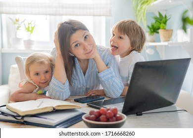 Female working from home with kids running and screaming, kitchen background