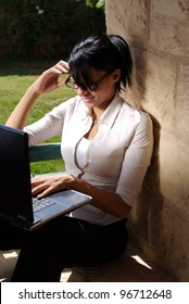 A female working on a lap top in a garden space