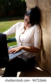 A female working on a lap top in a garden space and talking on a mobile phone