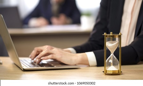 Female working on laptop at office, hourglass measuring time, efficiency at work, stock footage