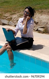 A female working on a pool edge and talking in a mobile phone