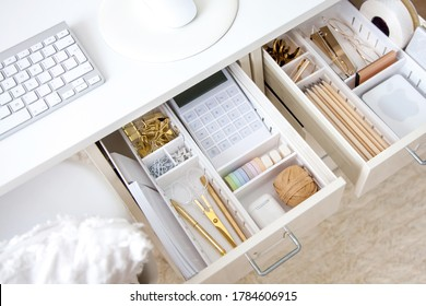Female workplace. White work table. The stylish gold stationery is arranged very neatly in the drawers of the desk. Japanese storage method.