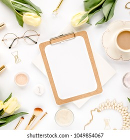 Female workspace with yellow tulip flowers, clipboard, women's fashion golden accessories, diary,  glasses on white background. Flat lay. Top view feminine background.