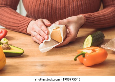 Female wrapping cheese into beeswax wraps at the kitchen