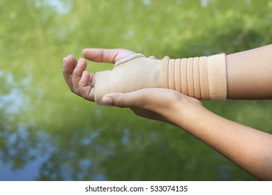 Female  with wrist pain in an Elastic Bandage exercise fingers with green background