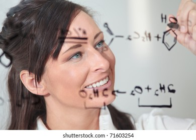 female writes out a chemistry equation.