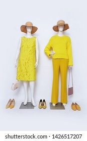 Female yellow clothing with sundress and yellow trousers ,straw hat, handbag on two mannequin isolated