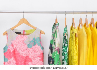 Female ,yellow shorts sweater ,shirt and skirt with floral pattern sundress isolated on hanger