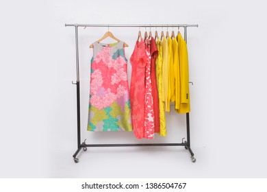 Female ,yellow shorts sweater ,shirt and skirt ,coat with floral pattern sundress isolated on hanger