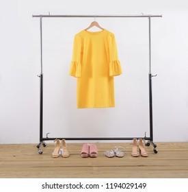 female yellow sundress, vest on hanger