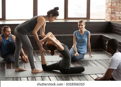 Female yoga instructor helping woman developing flexibility doing exercise at multi-ethnic group training, trainer assisting young girl teaching eka pada rajakapotasana or one legged king pigeon pose