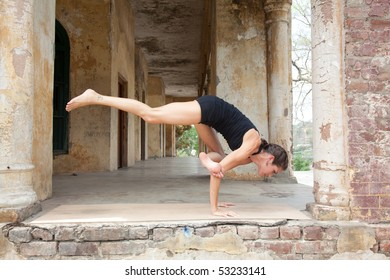 Female yoga teacher executing postures (asanas) at an old hotel in Rishikesh, India.