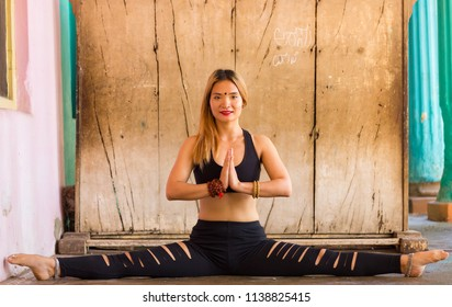 Female yoga teacher with legs split open and hands in namaste next to heart. Indian yogi girl in konasana pose wearing black sportswear. Flexibility concept of barefoot young woman