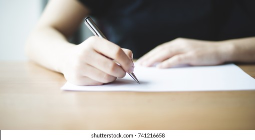 Female young hands write down goals or plans or tasks in a notebook on a wooden table.