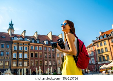 Female young traveler with backpack and photocamera in the old town market square in Warsaw, Poland