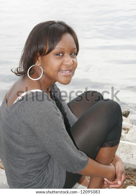 a female youth from Chad Africa sitting by the edge of the water