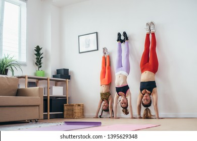 Females doing handstand pose near wall. Mother and daughters exercising at home, sport, family