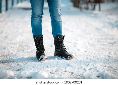 Female's feet in close-up, wearing boots with anti-slip protectors. Snow in the background. Copy space.