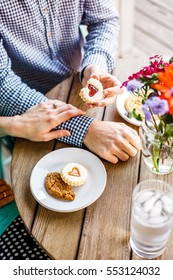 Female's hand with diamond ring crosses over her husband's arm while he hands her  a cookie with plates and additional cookies and a vase of flowers on the table.