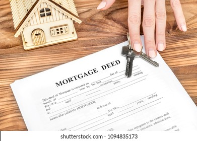 Female's hand giving mortgage deed and keys from house over table. Real estate concept.