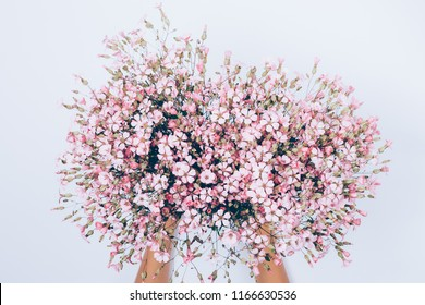 Female's hand holding big lush bouquet of pink gypsophilia flowers on white background, top view. Festive flat lay floral composition.