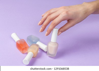 Female's hand holding bottles with colorful nail polish of purple background