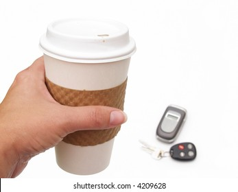 female's hand holding disposable coffee cup with keys and cell phone in background