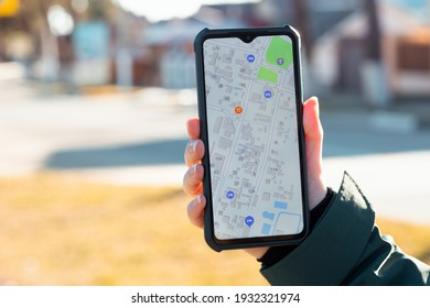 A female's hand holds a cellphone with an open online maps app. The concept of online navigators and applications for smartphones. Close up. Blurred background.