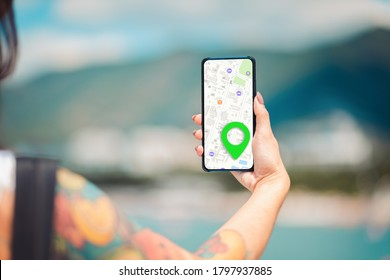 A females hand holds a smartphone with an online map app and a marked destination.View from the back.Concept of online navigation and modern technologies