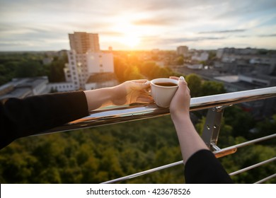 female's hand keeps cup with coffee or tea in hand in rays of sunset; woman on the roof and with cup of hot drink;