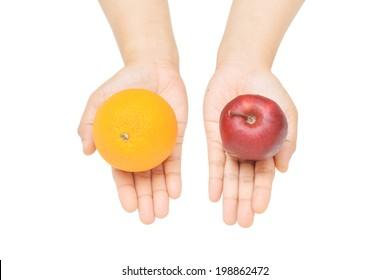 a female's hands gesture offering orange or apple.