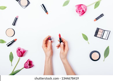 Female's hands holding open classic red lipstick among decorative cosmetics and blooming flowers on white table, top view. Flat lay composition of pink tulips and feminine makeup beauty products.