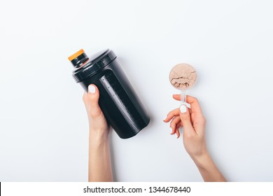 Female's hands holding scoop of chocolate protein powder and black plastic shaker to prepare sports drink for muscle growth, top view on white table.