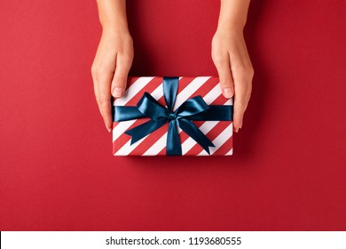 Female's hands holding striped gift box with blue ribbon on red background. Christmas, New Year, Valentine's day and birthday concept.
