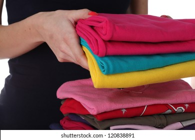 Female's hands laying down colorful clothes