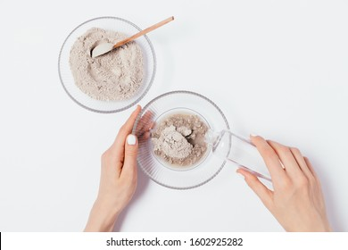 Female's hands pouring water into bowl with clay powder to make cosmetic cleansing face mask, top view