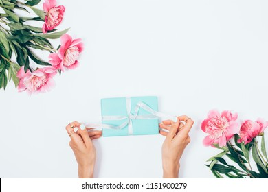 Female's hands unbinding ribbons on blue gift box near pink peony bouquets, view from top. Flat lay concept composition woman opening a present.