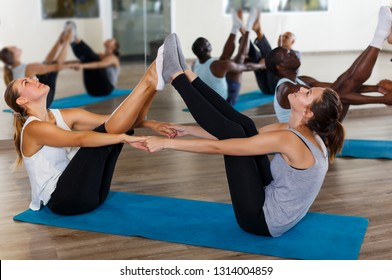 females and males doing stretching workout in pairs during group training at gym