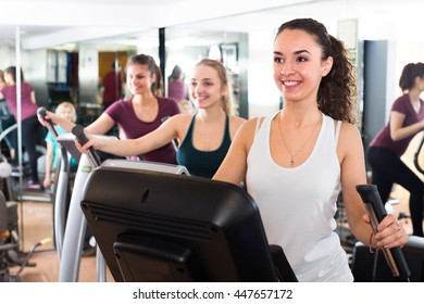 Females riding cardiovascular trainers in modern gym for women