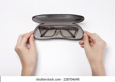 A female(woman, girl) hold a leather eye wear(glasses) case with glasses isolated white, top view.