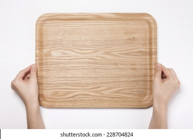 A female(woman, girl) hold a wooden tray isolated white, top view.