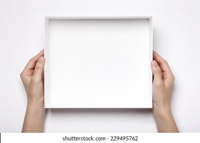 A female(woman, girl) two hands hold the empty(blank) white box isolated white, top view at the studio.