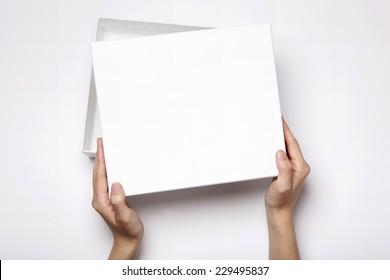 Eine Frau (Frau, Mädchen) zwei Hände halten und öffnen die leere(leere) weiße Box einzeln weiß, Draufsicht im Studio.