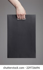 A female(woman) hand hold a black shopping bag(paper bag) at the studio.