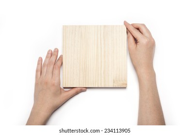 A female(woman) hand hold a empty(blank) wood sign(facade, panel) isolated white, top view at the studio.
