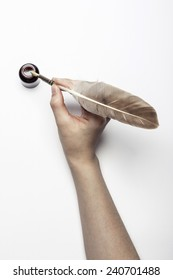 A female(woman) hand hold a feather quill pen with ink isolated white at the studio.