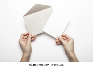 A female(woman) hand hold a grey envelope and post card isolated white at the studio.